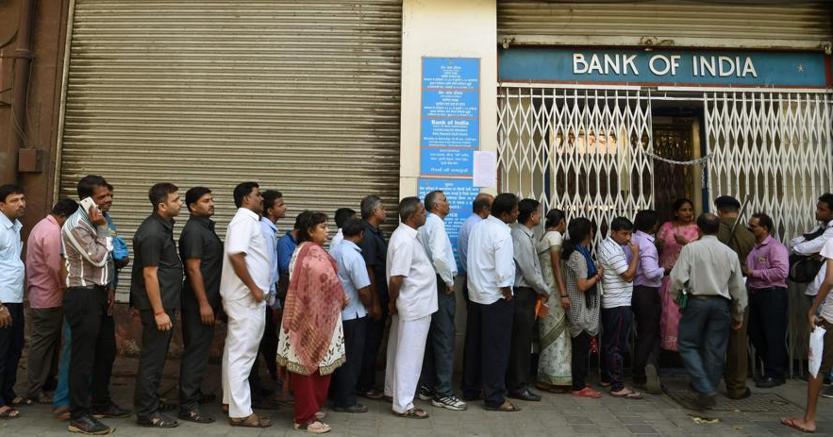 Indiani in fila davanti a una filiale della Bank of India di Mumbai